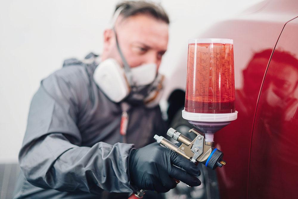Mechaniker lackiert Auto in rot