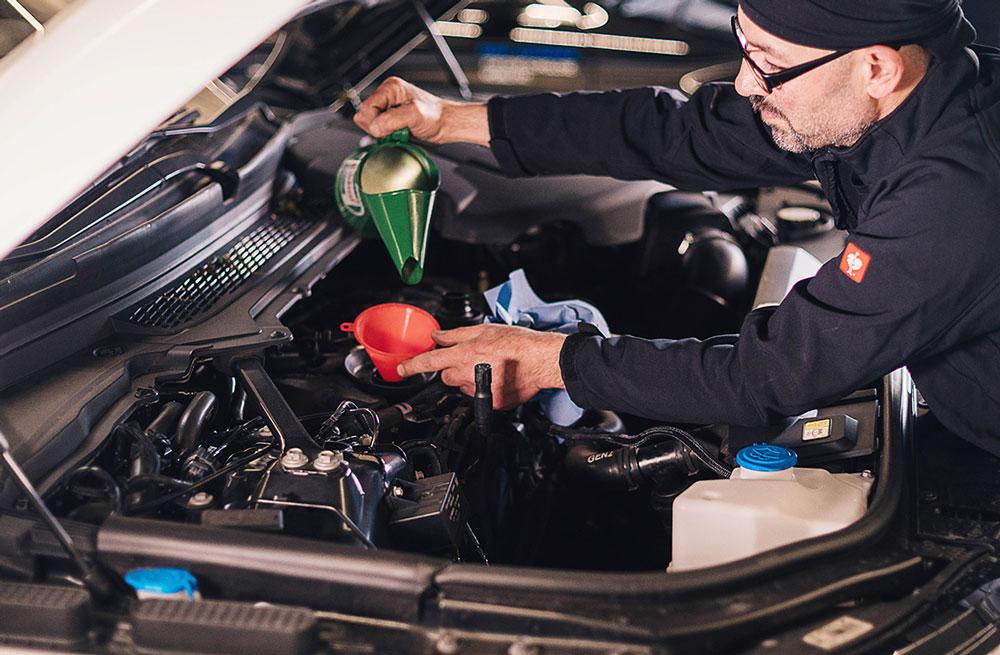 Mechaniker füllt das Öl nach
